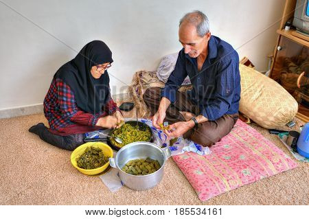 Bandar Abbas Hormozgan Province Iran - 15 april 2017: An elderly muslim couple is preparing a dish of Persian cuisine dolmeh sitting on the carpet at home.