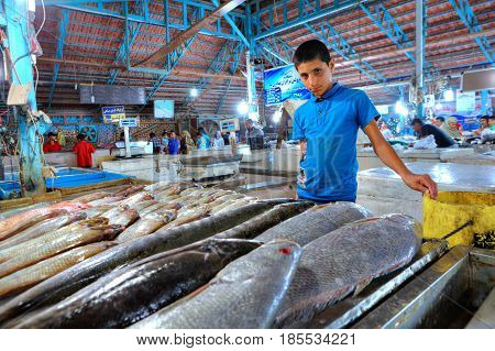 Bandar Abbas Hormozgan Province Iran - 15 april 2017: A trader boy stands near a counter with fresh fish in a covered fish market.