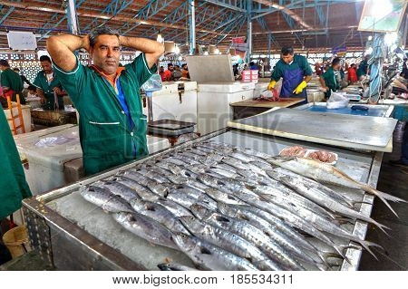 Bandar Abbas Hormozgan Province Iran - 16 april 2017: One seller of fish in green overalls in the indoor fish market.