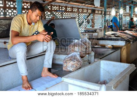 Bandar Abbas Hormozgan Province Iran - 16 april 2017: One young Iranian man sitting at the entrance to the fish market near the packages with shrimp and reads message on the smartphone screen.