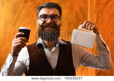 Bearded man long beard. Brutal caucasian unshaven happy smiling hipster with glasses and moustache holding black plastic coffee cup or mug and meal box on brown studio background