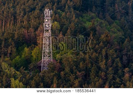 A telecommunication transmitter at the top of a wooded hill in aerial photography.