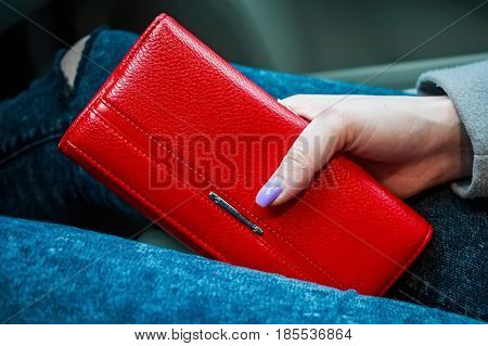Close up of woman's hands holding modern red women's wallet