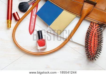 Woman's bag and it's content - nail file, polish, hair brush, book, notebook, perfume, mascara