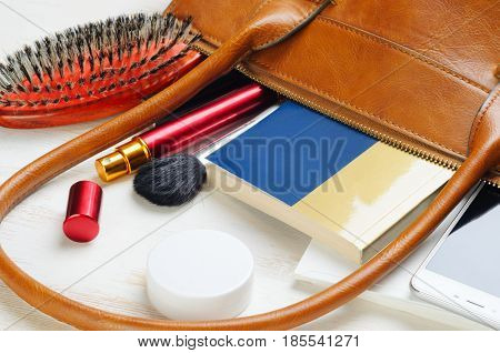 Woman's bag and it's content - nail file, polish, hair brush, book, notebook, perfume, mascara, napkins