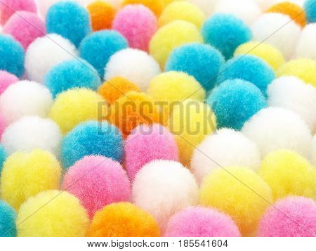 closeup colorful pom poms texture background, small multicolored fluffy ball for crafts and decoration, selective focus