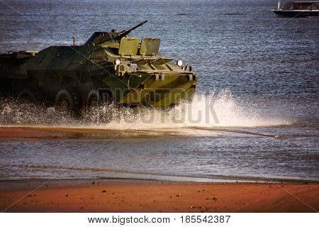 A Military Tank Rides The Water At Sea, Scattering Water Splashes