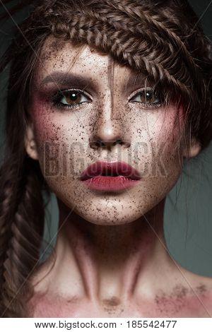 Beautiful strange girl with creative art make-up. Beauty face. Photo taken in studio