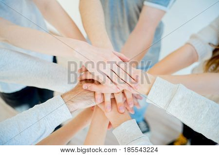 Group of people putting their hands together