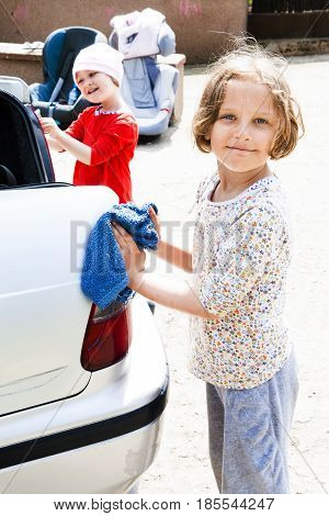 Sisters helping out with washing and cleaning a car.