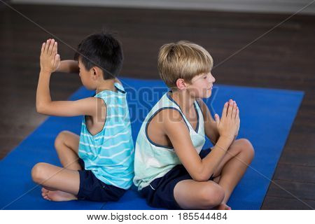 Side view of siblings performing yoga at home