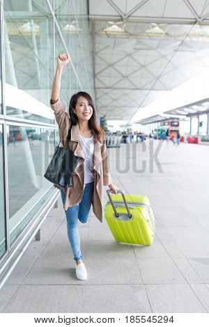 Thrilled woman go travel in Hong Kong airport