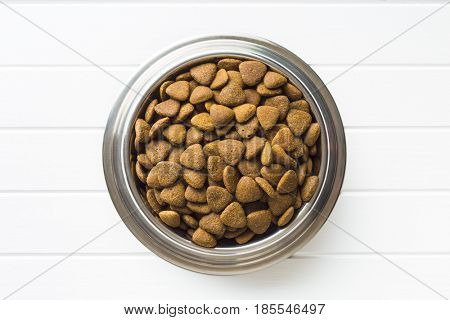 Dry kibble dog food in metal bowl. Top view.