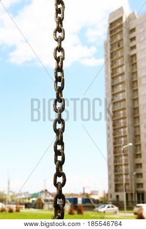 strong iron chain on blue sky and building