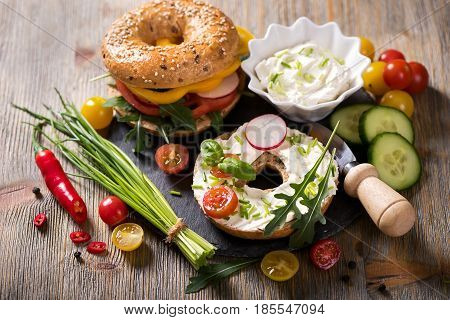 Vegetarian bagel sandwich with cream cheese fresh veggies and arugula healthy food lunch breakfast snack