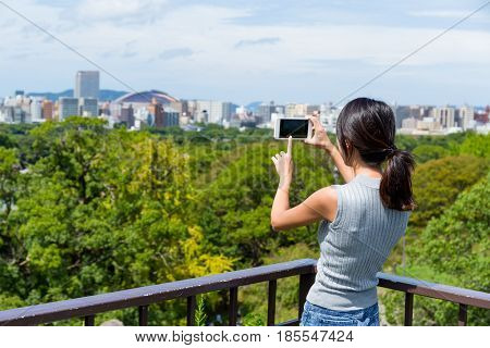 Woman taking photo with cellphone in fukuoka city
