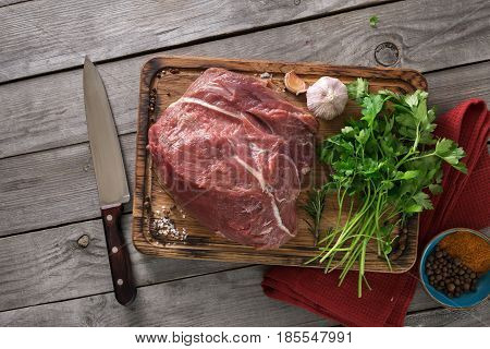 Raw meat. Fresh beef tenderloin on cutting board with parsley and spices. Top view