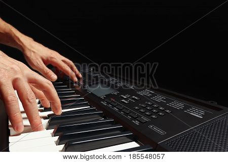 Hands of pianist play the keys of the synthesizer on a black background