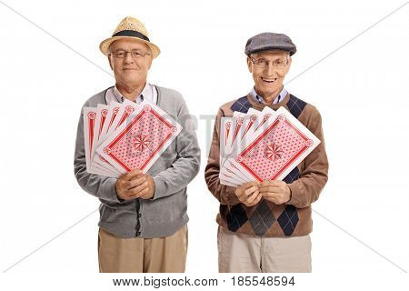 Two elderly men with playing cards looking at the camera and smiling isolated on white background