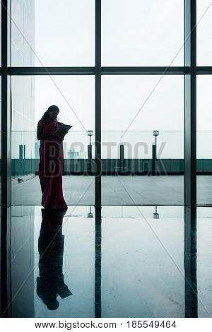Indian woman using a tablet on the corridor of a modern corporate building with tiled floor and transparent walls
