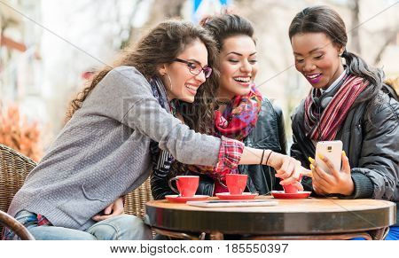 Multicultural group of women in cafe showing each other pictures on smart phone and chatting