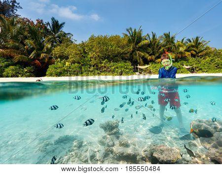 Split underwater photo of boy having fun in ocean enjoying snorkeling with tropical fish
