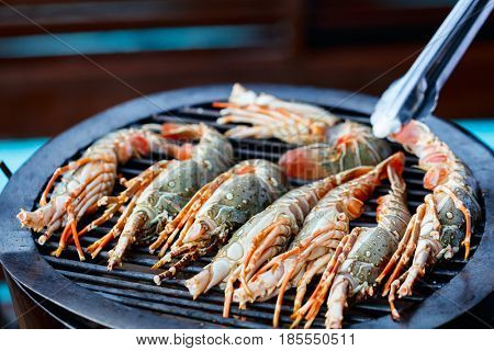 Close up of fresh lobsters and crayfish grilling on open fire