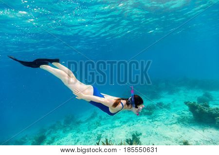 Underwater photo of woman snorkeling in a clear tropical water at coral reef