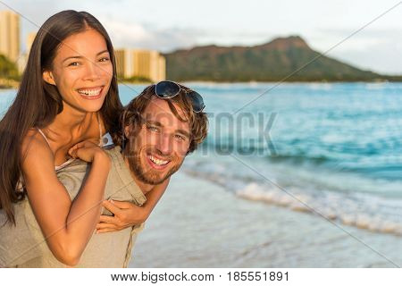 Couple in love having fun piggybacking on Hawaii beach. Healthy people portrait girlfriend and boyfriend hugging happy at sunset on Waikiki vacation, Honolulu, Hawaii. Multiracial relationship.