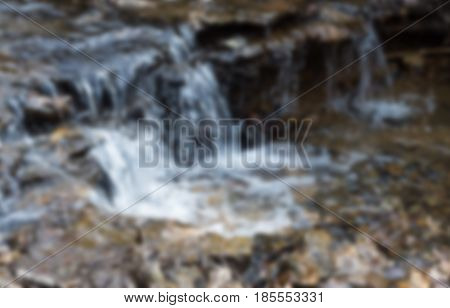 Natural flow of falling water. Blurred photo. Shallow creek in the wild. Horizontal rectangular background.