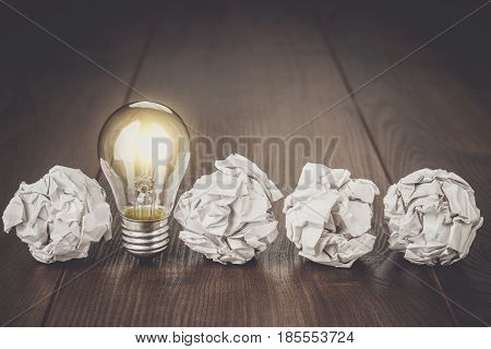 Great idea business concept. Business idea brainstorming concept with crumpled office paper. Great idea as light bulb standing on the office table. Business meeting concept. Business plan idea brainstorming concept.