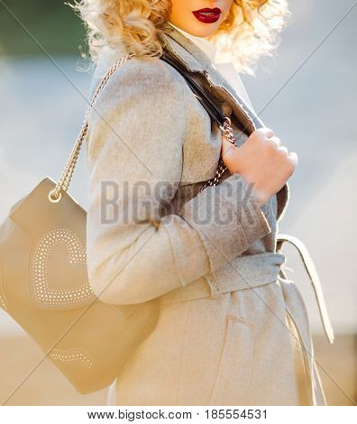 Young stylish hipster girl wearing modern trench coat walking in urban city with the fashionable shoulder bag, autumn.