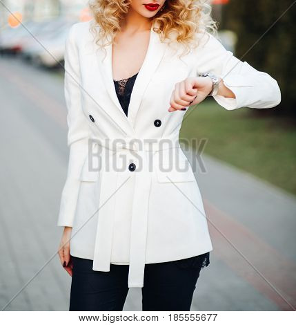 Stylish young blond woman with curly hair in white fashion trend coat with buttons, fall, looks at his watch, hurries out. Stylish looks, expensive. Fashion, beauty, style, trend.
