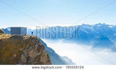 A male figure on top of a mountain. Grandiose panorama of mountains and clouds from the top.