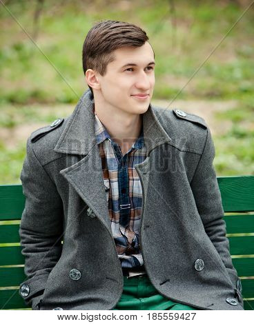 young man in a gray coat sitting on the bench
