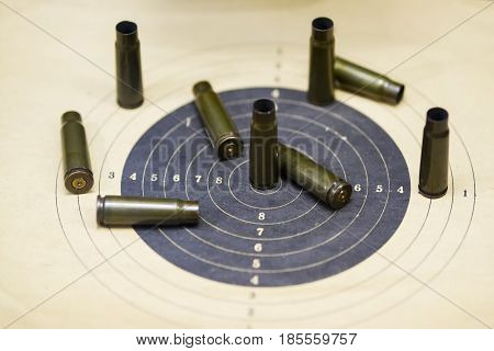 Weapon sleeves from the gun bullet at paper target, background