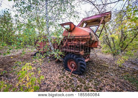 Abandoned combine vehicle in collective farm near Zymovyshche ghost village in Chernobyl Exclusion Zone Ukraine
