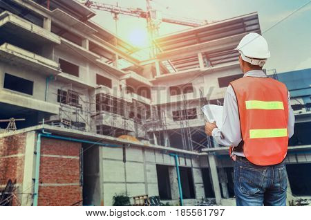 Architect looking at buiding site hand holding blueprints and sunshine background