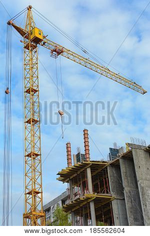 Yellow construction cranes and unfinished building with metal-concrete structure on a background of blue sky with white clouds. Vertical photo.
