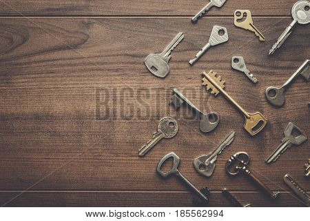 many different keys on brown table. keys with copy space. keys background. different keys view from above