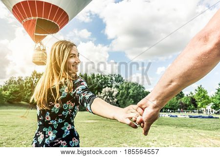 Happy young woman wants to make balloon tour holding boyfriend's hand - Follow me future together and love concept - Couple of lovers having fun in park outdoor - Focus on hand - Contrast filter