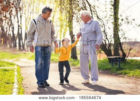 Two grandfather walking with the grandson in the park
