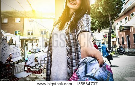 Pov view of young female seller giving short jeans in clothes weekly market on summer time - Cheerful sale person working in his second hand stand outdoor - Shopping concept - Focus on her face