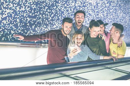 Happy friends taking selfie snapshot with instant camera on subway metro train escalator - Young people having fun before taking tube train - Focus on woman making photo - Vintage matte filter