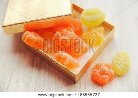 colorful jelly candy in golden present box.white wooden table.