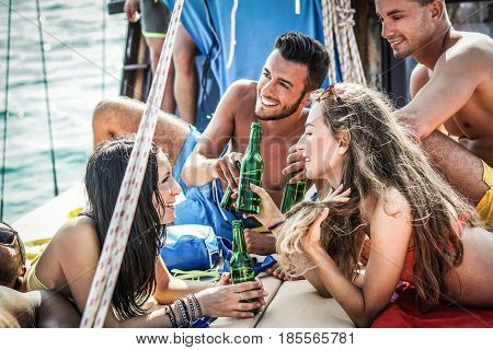 Happy friends toasting beers and chilling beers in boat vacation trip - Young rich people having fun in holidays - Summeryouth and friendship concept - Focus on girls face - Contrast filter