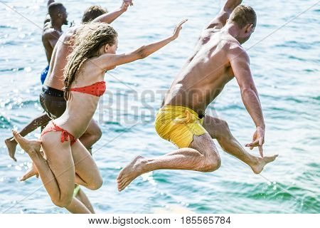 Young friends diving in sea water from sailing boat - Rich people having fun in summer excursion day - Vacation and friendship concept - Focus on right man back and bottom leg - Vintage filter
