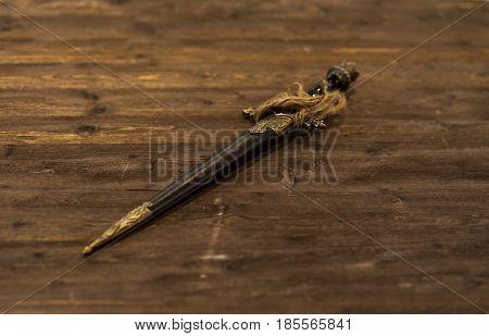 Ancient short sword dagger old knife on wooden background. defocused.