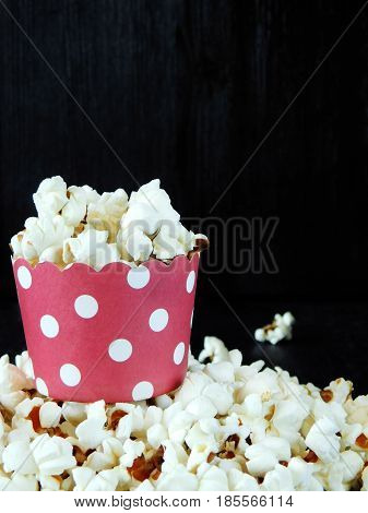 Popcorn in a red paper cup on a black background. Empty space for a text