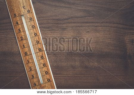 wooden thermometer on the brown table background